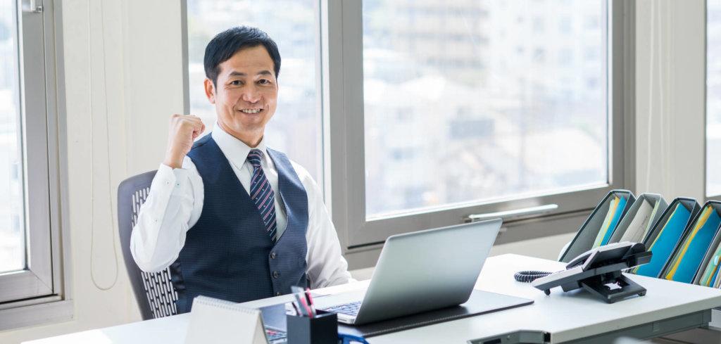 ノートパソコンの前でガッツポーズしている笑顔の男性