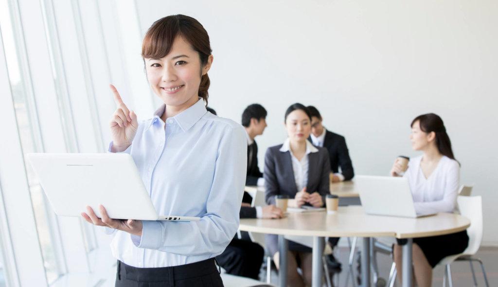 ノートパソコンを持って人差し指を立てて微笑む女性